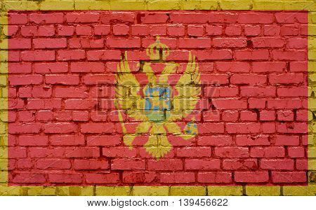 Flag of Montenegro painted on brick wall background texture