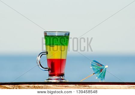 A glass with colorful cocktail on the background of the sea umbrella for cocktails