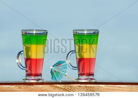 Two glasses with colorful cocktails on the background of the sea umbrella for cocktails