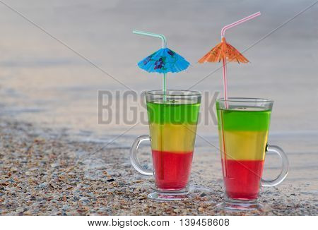 Two cocktails with straws in the sand on the seashore