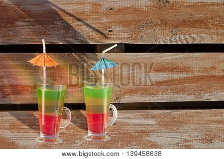Two glasses with colored cocktails and straws on wooden planks space for text