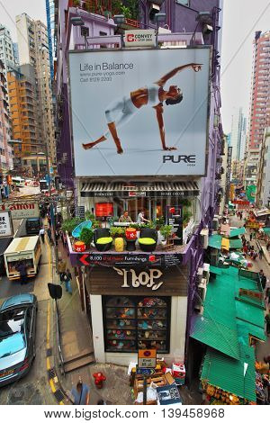HONG KONG - DECEMBER 11, 2014: Hong Kong Special Administrative Region. Crowded shopping street in Hong Kong. The building's facade is decorated with a magnificent advertisement yoga