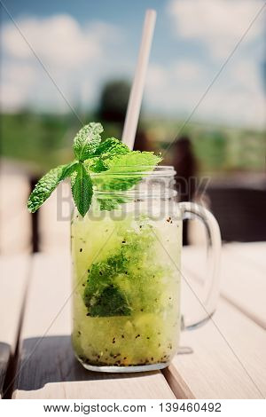 Refreshing cocktail with pepermint and kiwi .