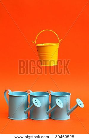 Gardening concept. Few blue watering cans on red background. One yellow bucket flying above