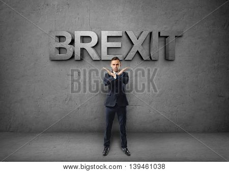 Young businessman making X sign with his arms on the concrete backround with 'brexit' word. Prohibitions and restrictions. Body language. Office clothes. British withdrawal.