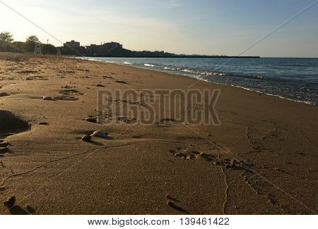 Sandy beach with foot prints at the lake shore during summer
