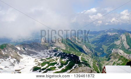 Mountain world in Switzerland, view from Säntis on the Alpstein-Massif with the Lake Seealp in Appenzellerland, steep rocks and snow fields,