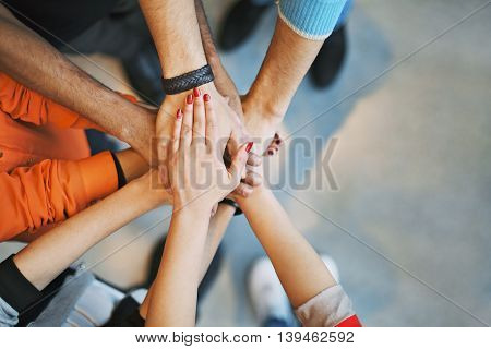 Multiethnic group of young people putting their hands on top of each other.
