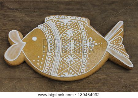 Decorated gingerbread with white pattern on wooden background