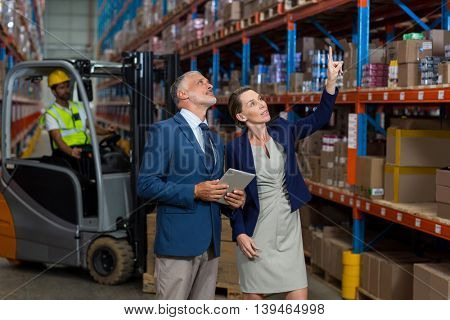 Managers are looking shelves and pointing in a warehouse