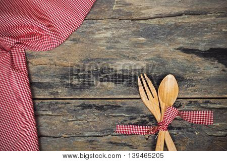 Wooden fork and spoon with red fabric on old wooden background