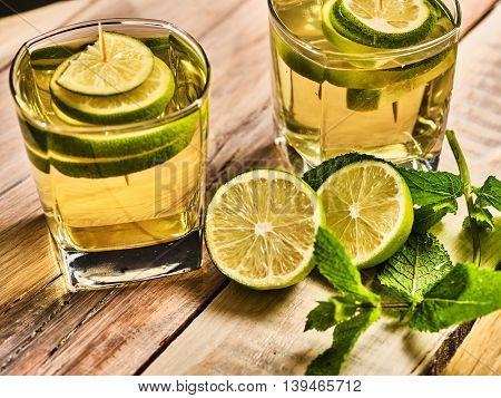Country alcohol cocktail. On wooden boards two glasses with green transparent drink and half lime . Drink one two hundred forty-three mojito with mint leaf . Country life. Boards background. Top view.