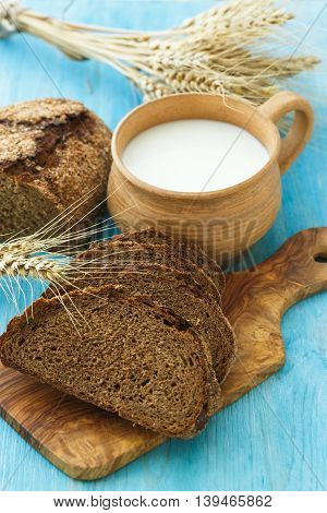 Homemade bread milk and ripe ears of wheat on a blue wooden background place for text