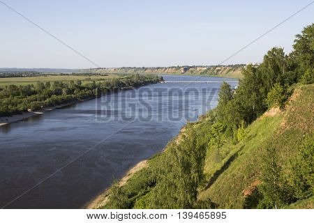 View from the high bank of the wide river. The bridge in the distance
