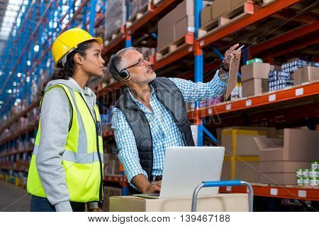 Manager and worker are looking shelves in a warehouse