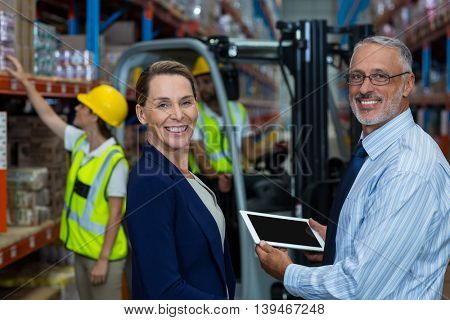 Business people are holding tablet and looking the camera in a warehouse