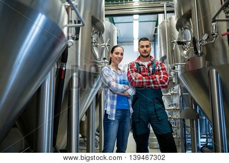 Portrait of brewers standing with arms crossed at brewery