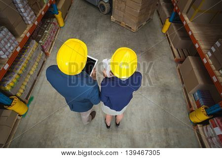 High angle view of managers with hard hat holding tablet and clipboard in a warehouse