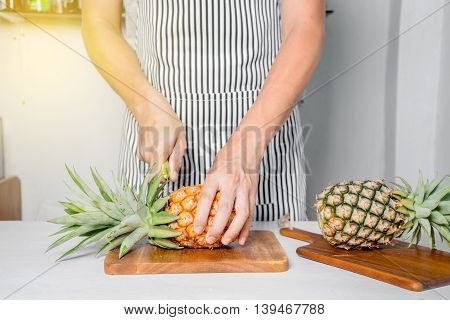 Man Standing Behind Bar Counter Cutting A Pineapple On Chopping Board.