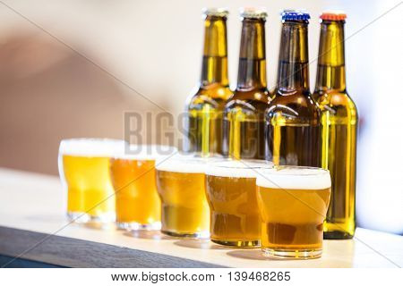 Arranged beer glasses and bottles on the bar counter at restaurant