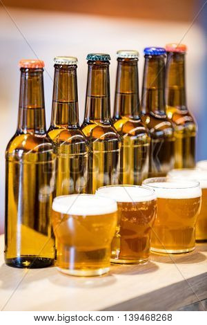 Close-up of arranged beer glasses and bottles on the bar counter at restaurant