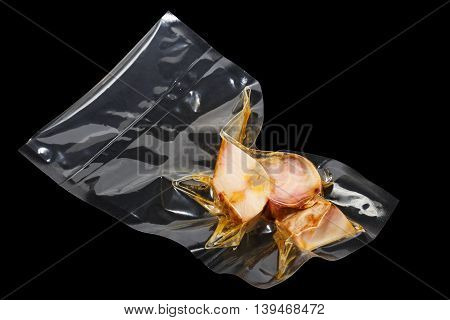 vacuum packaged pieces of sturgeon on the black background