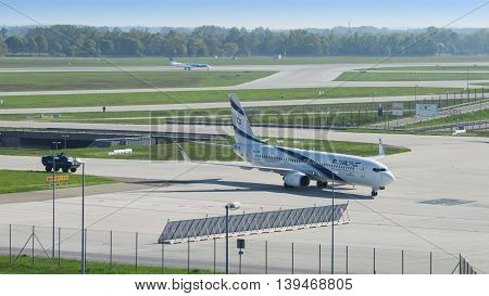 Munich Germany - May 6 2016: Israeli airline El Al plane landed in international airport and taxiing from runway to terminal accompanied by security armored vehicle.