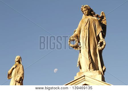 Statue in the Cemetery of Recoleta with the Moon in the background Buenos Aires Argentina.