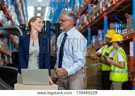 Portrait of happy managers are looking each other and smiling in warehouse