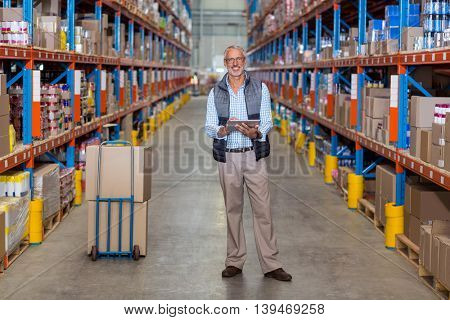View of manager is smiling and posing to the camera during work in warehouse