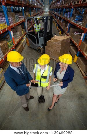 High angle view of managers talking with a worker in a warehouse