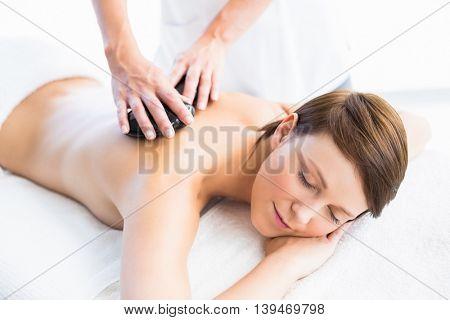 Beautiful woman enjoying hot stone massage from masseur at spa
