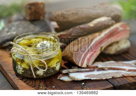 Sliced bacon together with other kinds of cooked meat and Chevre cheese on a wooden desk
