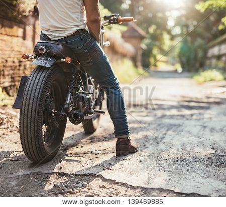 Cropped shot of young man on his motorcycle on dirt road. Low section view with focus on motorbike and male leg.