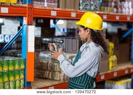 Female worker wearing yellow helmet scanning documents in warehouse