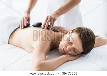Relaxed woman receiving hot stone massage from masseuse at spa