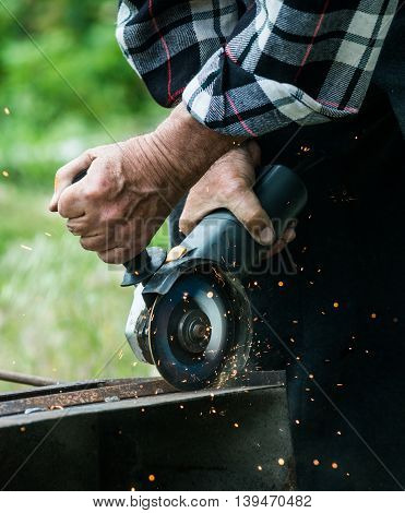 Closeup of worker using a grinder on a metal plate