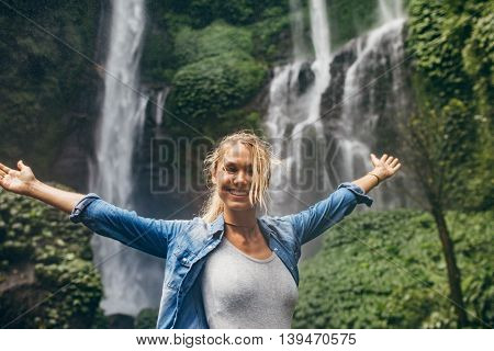 Portrait of young woman standing in front of a waterfall in forest with her hands outstretched. Caucasian female tourist with tropical waterfall in background.