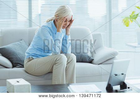 Sad senior woman sitting on sofa at home