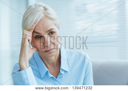 Sad senior woman looking away at home