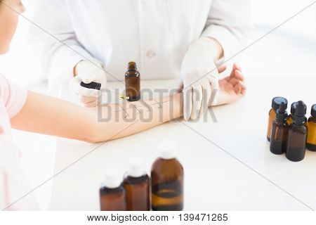Midsection of doctor dropping medicine on woman hand at clinic