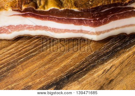 Traditional smoked bacon on vintage wooden board