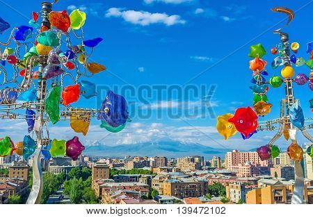 YEREVAN ARMENIA - MAY 29 2016: The Ararat Mount in clouds and cityscape of Yerevan through the glass weathervane trees on the upper level of Cascade on May 29 in Yerevan.