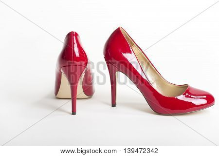 pair of red high heels on white background