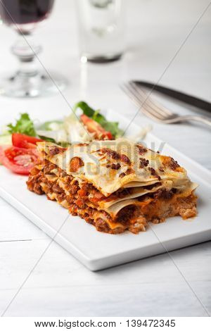 italian lasagna on a square plate with wine