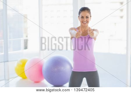 Portrait of smiling happy woman showing thumbs up sign at fitness studio