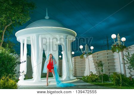 Young girl with pretty face in sexy red dress in blue bridal veil near white rotunda on natural dark night sky background outdoor