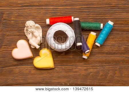 Many bobbins of bright colorful cotton threads for sewing homemade cookies in heart shape and hank of yarn with angel figure on wooden background