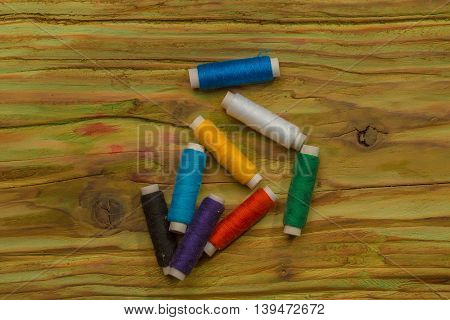 Many bobbins of bright colorful cotton threads for sewing laying on wooden background