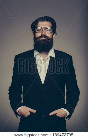 Handsome man bearded hipster male wears vintage glasses black suit with hands in pockets on grey wall